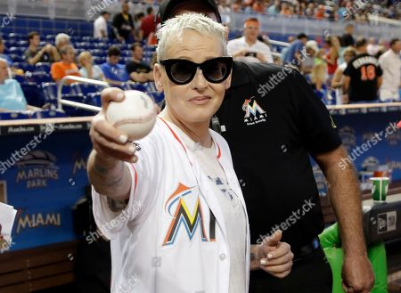 Stock Image of Actress Lori Petty holds a baseball before throwing a ceremonial pitch before a baseball game between the Miami Marlins and Chicago Cubs, in Miami. Petty was in the 1992 film A League of Their Own