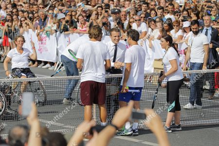 French resident Emmanuel Macron after played wheelchair tennis with Michael Jeremiasz partner, is greated Fabrice Santoro during the Olympic Days