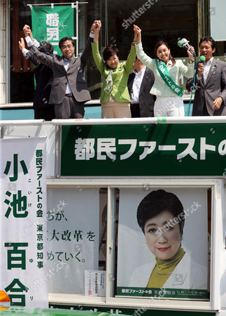"""Tokyo Governor Yuriko Koike (2nd L) raises hands with her party """"Tomin First no Kai"""" candidate Airi Ryuen (R) and her party lawmaker Masaru Wakasa as she delivers a campaign speech for the upcoming Tokyo Metropolitan Assembly election in Tokyo"""