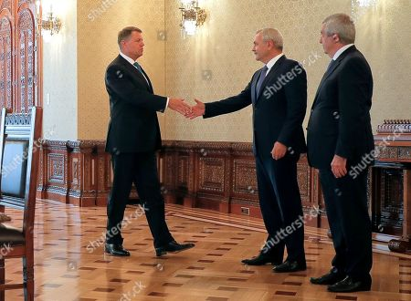 Romanian President Klaus Ioannis, left, shakes hands with leader of the ruling Social Democratic Party Liviu Dragnea, center, as Calin Popescu Tariceanu, who heads the junior Alliance of Democrats and Liberals, stands by at the Cotroceni presidential palace in Bucharest, Romania, . The Social Democratic Party nominated lawmaker Mihai Tudose, a 50-year-old economy minister in the previous government and an ally of Liviu Dragnea, to be the next prime minister