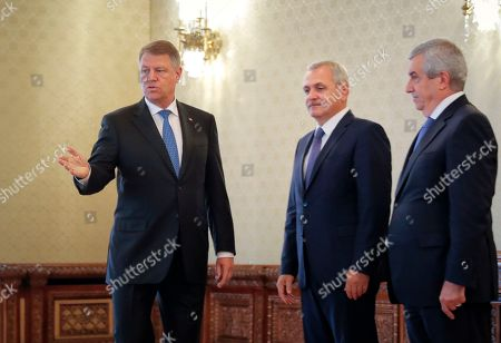 Romanian President Klaus Ioannis, left, gestures next to the leader of the ruling Social Democratic Party Liviu Dragnea, center, as Calin Popescu Tariceanu, who heads the junior Alliance of Democrats and Liberals, stands by at the Cotroceni presidential palace in Bucharest, Romania, . The Social Democratic Party nominated lawmaker Mihai Tudose, a 50-year-old economy minister in the previous government and an ally of Liviu Dragnea, to be the next prime minister