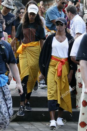 Former US First Lady Michelle Obama (R) and her daughter Malia Obama (L) visit the Tirta Empul Temple during a family holiday in Bali, Indonesia, 27 June 2017. The Obamas are in Bali as part of a ten-day family holiday in Indonesia.