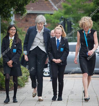 Stock Picture of Theresa May meets head teacher Dr Helen Holman and pupils Miya Herbert (dark hair) and Katie Davies (lighter Hair)