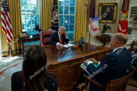 President Donald Trump, accompanied by Deputy National Security Adviser Dina Powell and National Economic Council Director Gary Cohn, talks with new Irish Prime Minister Leo Varadkar during a telephone call, in the Oval Office of the White House in Washington