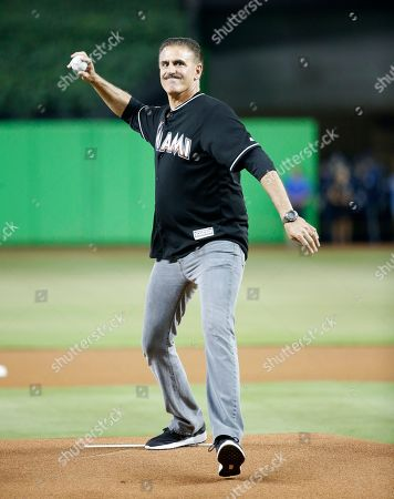 Ron Magill, the goodwill ambassador and communications director for Zoo Miami, throws out a ceremonial first pitch before the start of a baseball game between the Miami Marlins and the New York Mets, in Miami