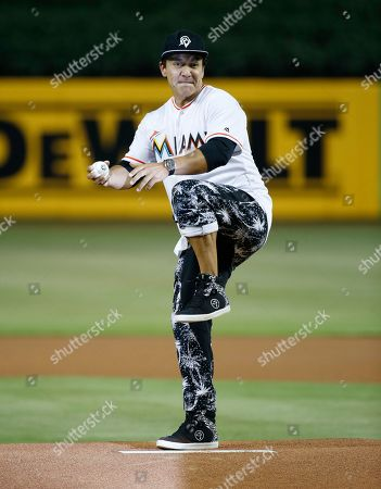 Beto Perez, the inventor of the fitness program Zumba, throws out a ceremonial first pitch before the start of a baseball game between the Miami Marlins and the New York Mets, in Miami