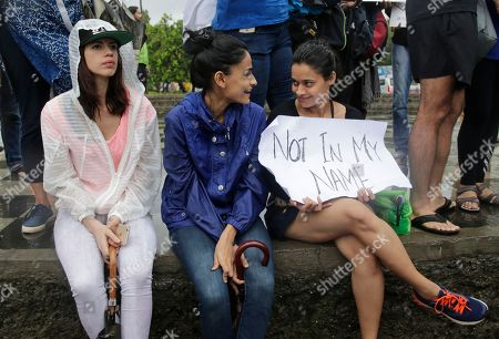 Bollywood actress Kalki Koechlin, left, sits with others during a protest against a spate of violent attacks across the country targetting the country's Muslim minority, in Mumbai, India, . Thousands of protestors gathered in different cities to decry the silence of India's Hindu right-wing government in the face of the public lynchings and violent attacks on at least a dozen Muslim men and boys since it was voted to power in 2014