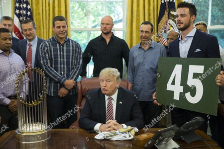 US President Donald Trump (C) sits at his desk between Chicago Cubs third baseman Chris Bryant (R) and the Commissioner's Trophy while hosting the Chicago Cubs in the Oval Office of the White House in Washington, DC, USA, 28 June 2017. Trump hosted the Chicago Cubs to congratulate them on winning the 2016 World Series.