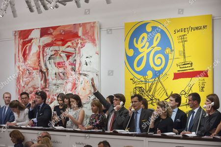 Sotheby's staff bid on behalf of telephone clients in front of  'The Girl Who Had Everything', 1998, by Cecily Brown sold for a hammer price of GBP1.55m (estimate GBP0.8-1.2m) and 'Sweet Pungent', 1984-85, a collaborative work by Andy Warhol and JEAN-MICHEL BASQUIAT sold for a hammer price of GBP3.8 m (estimate GBP1.4-1.8m) at Sotheby's Contemporary Art evening sale in New Bond Street, which featured pioneering works from the Pop Art genre.