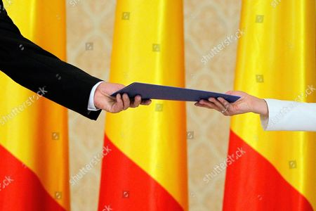 Romania's President Klaus Iohannis (L) hands a signed oath to an assistant during a swearing-in ceremony for new government headed by Prime Minister Mihai Tudose at Cotroceni palace in Bucharest, Romania, 29 June 2017. The previous government, directed by Sorin Grindeanu, was ousted after a no-confidence vote was pushed in the previous week by PSD in parliament.