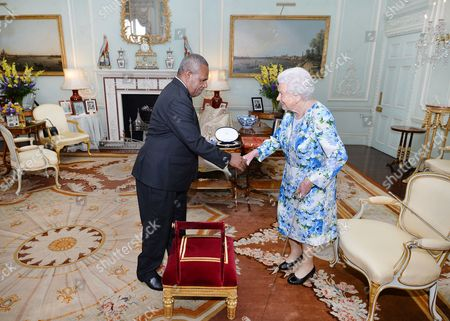 Queen Elizabeth II shakes hands with Sir Robert Dadae the Governor General of Papua New Guinea, during a private audience where he was knighted at Buckingham Palace