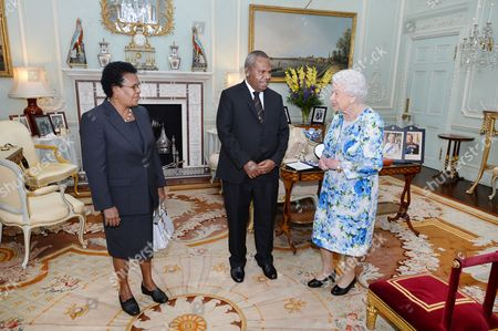 Queen Elizabeth II talks with Sir Robert Dadae the Governor General of Papua New Guinea, and Lady Dadae during a private audience where he was knighted at Buckingham Palace
