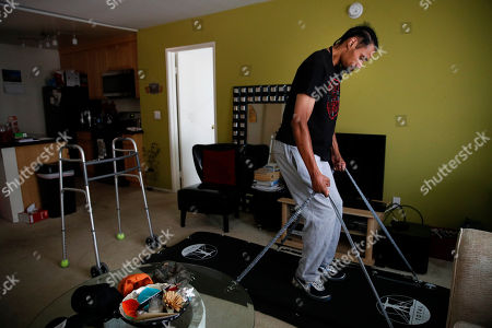 Jamie Nieto, a two-time Olympic high jumper who is recovering from a spinal cord injury, does squats on a board in his apartment ahead of his July wedding, in Los Angeles. Nieto proposed to his fiancée while in a wheelchair as he recovered from a spinal cord injury after a mistimed backflip. Up to 130 steps with no assistance, he fully intends to walk her down the aisle at their wedding on July 22