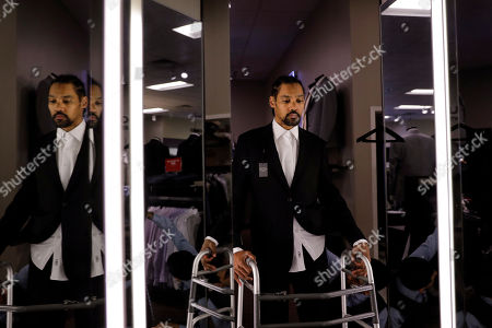 Jamie Nieto, a two-time Olympic high jumper who is recovering from a spinal cord injury he suffered 14 months ago after a mistimed backflip, looks in the mirror while getting his tuxedo fitted ahead of his July wedding, in Pasadena, Calif. On good days, Nieto can shuffle 130 steps without a cane or walker. That's an important distance for the two-time Olympic high jumper. By his estimation, 130 paces takes him from the altar to the church door for his wedding on July 22