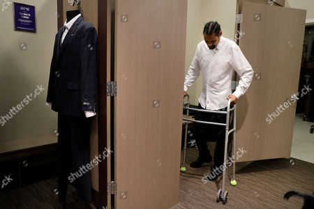 """Jamie Nieto, a two-time Olympic high jumper who is recovering from a spinal cord injury, uses his walker as he steps out of a fitting room while getting his tuxedo fitted ahead of his July wedding, in Pasadena, Calif. Nieto was paralyzed last year when he celebrated by doing his trademark backflip during a training session. """"My short-term goal is to walk at our wedding. That's what I'm working towards,"""" said Nieto"""