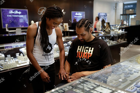 Jamie Nieto, Shevon Stoddart Two-time Olympic high jumper Jamie Nieto, right, and his fiancee Shevon Stoddart, a Jamaican hurdler, smile as they look at their wedding rings at a jewelry store ahead of their July wedding, in Torrance, Calif. Nieto proposed to the Jamaican hurdler while in a wheelchair as he recovered from a spinal cord injury after a mistimed backflip. Up to 130 steps with no assistance, he fully intends to walk her down the aisle at their wedding on July 22
