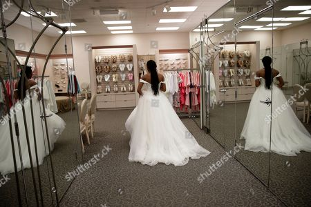 """Shevon Stoddart, a 34-year-old Jamaican hurdler, tries on a wedding dress at a bridal shop ahead of her July wedding with two-time Olympic high jumper Jamie Nieto, who is recovering from a spinal cord injury he suffered after a mistimed backflip during a training session, in Burbank, Calif. """"The wedding will be an amazing day for us, and our family and friends and supporters who've helped us get through this,"""" said Stoddart"""