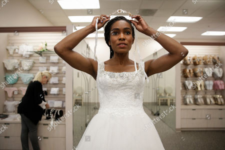 """Shevon Stoddart, a 34-year-old Jamaican hurdler, tries on a tiara while getting her wedding dress fitted ahead of her July wedding with two-time Olympic high jumper Jamie Nieto, who is recovering from a spinal cord injury after a mistimed backflip, in Burbank, Calif. """"The wedding will be an amazing day for us, and our family and friends and supporters who've helped us get through this,"""" said Stoddart"""