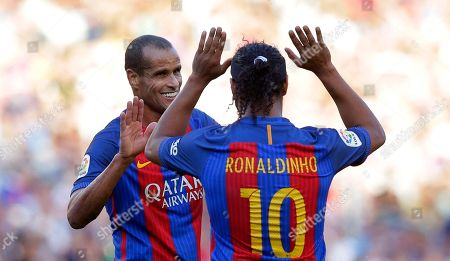 Ronaldinho, Rivaldo Former FC Barcelona player Ronaldinho, right, gestures to his teammate Rivaldo during the friendly soccer match between FC Barcelona legends and Manchester United legends at the Camp Nou stadium in Barcelona, Spain, Friday, June, 30, 2017