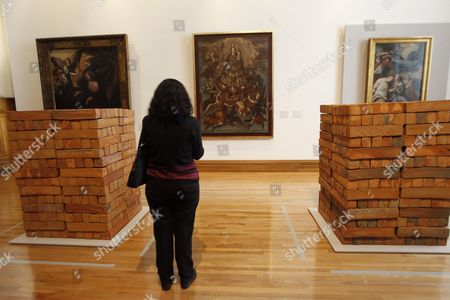 A visitor stands between two untitled works of Mexican contemporary artist Bosco Sodi during the exhibition 'Por los siglos de los siglos' (lit. For the centuries of the centuries) at the National Museum of Art in Mexico City, Mexico, 30 June 2017.