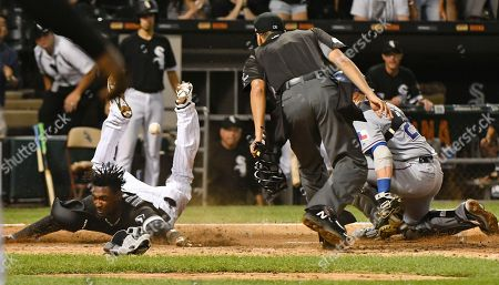 Gabe Morales, Alen Hanson, Jonathan Lucroy As home plate umpire Gabe Morales watches, Chicago White Sox's Alen Hanson scores past Texas Rangers catcher Jonathan Lucroy during the ninth inning of a baseball game in Chicago on