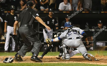 Gabe Morales, Alen Hanson, Jonathan Lucroy As home plate umpire Gabe Morales watches, Chicago White Sox's Alen Hanson, back right, scores past Texas Rangers catcher Jonathan Lucroy (25) during the ninth inning of a baseball game in Chicago on