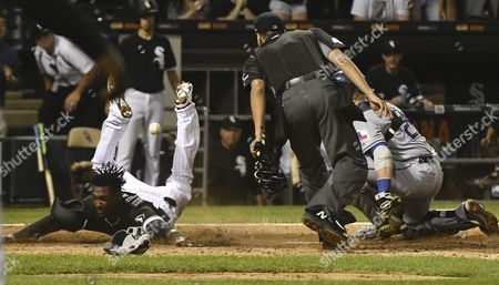 Gabe Morales, Alen Hanson, Jonathan Lucroy As home plate umpire Gabe Morales watches, Chicago White Sox's Alen Hanson, left, scores past Texas Rangers catcher Jonathan Lucroy (25) during the ninth inning of a baseball game in Chicago on