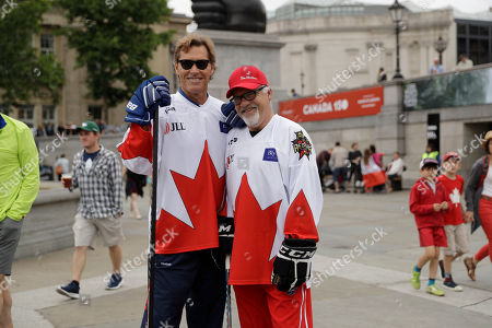 "Retired Canadian professional ice hockey players Ron Duguay, left, and Dennis Maruk pose for photographs before coaching children in a hockey skills workshop during a ""Canada 150"" celebration in Trafalgar Square, London, . Saturday is Canada Day, and this year marks the country's national milestone of 150 years since Confederation"