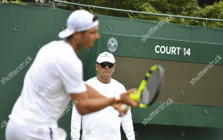 Rafael Nadal practices while is coach Toni Nadal looks on