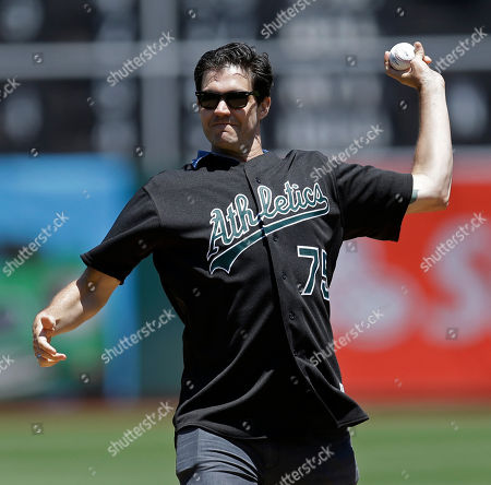Former Oakland Athletics pitcher Barry Zito throws out the ceremonial first pitch before a baseball game against the Atlanta Braves, in Oakland, Calif