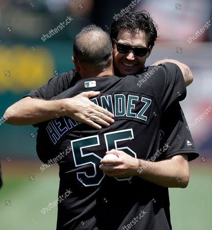Stock Image of Barry Zito, Ramon Hernandez Former Oakland Athletics pitcher Barry Zito, right, embraces former A's catcher Ramon Hernandez (55) after throwing out the ceremonial first pitch before a baseball game against the Atlanta Braves, in Oakland, Calif