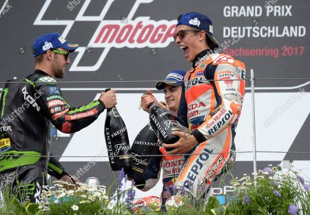 Stock Photo of Moto GP rider Marc Marquez of Spain, right, celebrates on the podium after winning the German Motorcycle Grand Prix at the Sachsenring circuit in Hohenstein-Ernstthal, Germany, . At left is Jonas Folger of Germany who finished second and center is Dani Pedrosa of Spain who was third