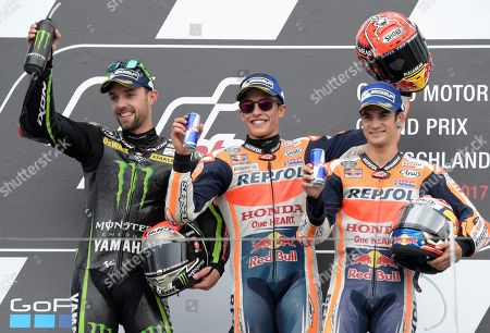 Stock Image of Moto GP riders Jonas Folger of Germany, Marc Marquez of Spain, and Dani Pedrosa of Spain, from left to right, pose on the podium after winning the German Motorcycle Grand Prix at the Sachsenring circuit in Hohenstein-Ernstthal, Germany, . Marquez won the race, Folger finished second Pedrosa was third