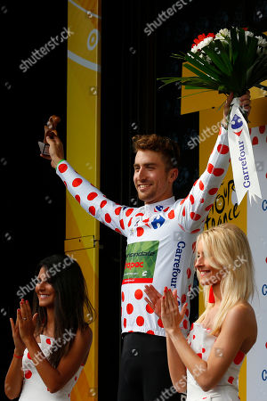 Taylor Phinney of the U.S., wearing the best climber's dotted jersey, celebrates on the podium after the second stage of the Tour de France cycling race over 203.5 kilometers (126.5 miles) with start in Dusseldorf, Germany, and finish in Liege, Belgium