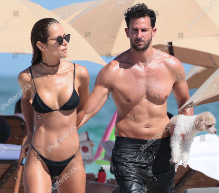 Stock Image of Natalia Borges in a bikini with her fiance Michael and their dog at the beach