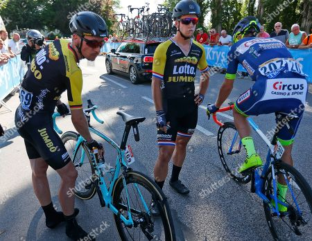 Netherlands' Dylan Groenewegen, center, and teammate Germany's Robert Wagner, left, wait for spare bicycles after crashing during the fourth stage of the Tour de France cycling race over 207.5 kilometers (129 miles) with start in Mondorf-les-Bains, Luxembourg, and finish in Vittel, France, . Far right is New Zealand's Dion Smith, also implicated in the crash