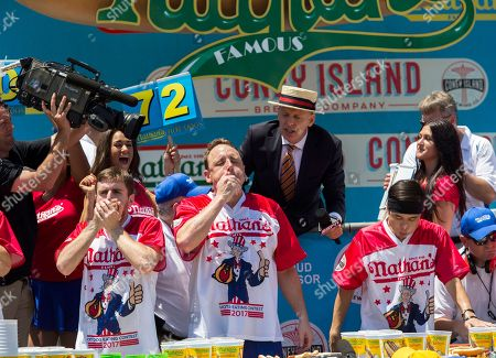 Carmen Ciccotti, left, Joey Chestnut, center, and Matt Stonie compete in the Nathan's Famous Hotdog eating contest, in Brooklyn, New York. Chestnut ate 72 hotdogs in 10 minutes to claim his 10th win