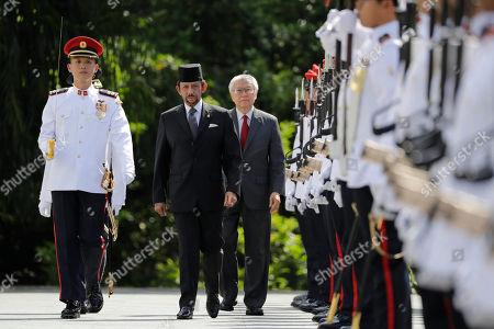 Brunei's Sultan Hassanal Bolkiah, center, and with Singapore's President Tony Tan, center right, inspect honor guards during a welcome ceremony at the Istana, in Singapore
