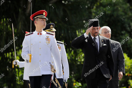 Brunei's Sultan Hassanal Bolkiah, center, and with Singapore's President Tony Tan, center right, inspect the honor guard during a welcome ceremony at the Istana, in Singapore