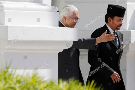 Singapore's President Tony Tan accompanies Brunei's Sultan Hassanal Bolkiah, right, as they proceed to inspect honor guards during a welcome ceremony at the Istana, in Singapore