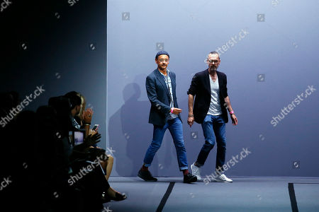 Dutch fashion designers Viktor Horsting, left, and Rolf Snoeren acknowledge applause from the audience after Viktor and Rolf's Haute Couture Fall/Winter 2017/2018 fashion collection presented in Paris