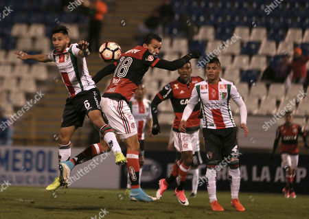 Leandro Damiao of Brazil's Flamengo, center, jumps for the ball with Diego Torres of Chile's Palestino during a Copa Sudamericana soccer match in Santiago, Chile