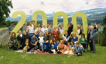 Emmerdale cast photgraph celebrating it's 2000th episode. This includes: Zak Dingle, as played by Steve Halliwell ; Biff Fowler, as played by Stuart Wade ; Sam Dingle, as played by James Hooton ; Ned Glover, as played by Johnny Leeze ; Jan Glover, as played by Roberta Kerr ; Daniel Weir, as played by Matthew Marsden ; Amos Brearly, as played by Ronald Magill ; Terry Woods, as played by Billy Hartman; Seth Armstrong, as played by Stan Richards ; Betty Eagleton, as played by Paula Tilbrook ; Alan Turner, as played by Richard Thorp ; Frank Tate, as played by Norman Bowler ; Chris Tate, as played by Peter Amory ; Kim Tate, as played by Claire King ; Vic Windsor, as played by Alun Lewis ; Viv Windsor, as played by Deena Payne ; Eric Pollard, as played by Christopher Chittell ; Nellie Gough, as played by Sandra Gough ; Butch Dingle, as played by Paul Loughran ; Tina Dingle, as played by Jacqueline Pirie ; Dave Glover, as played by Ian Kelsey ; Jack Sugden, as played by Clive Hornby ; Sarah Sugden, as played by Alyson Spiro ; Linda Glover, as played by Tonicha Jeronimo ; Rachel Tate, as played by Glenda Mackay; Dolores Sharp, as played by Samantha Hurst ; Kathy Tate, as played by Malandra Burrows.