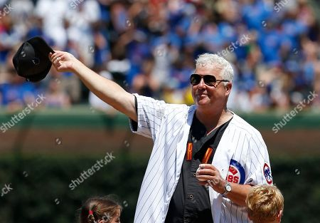 Actor William Petersen waves to the crowd before throwing out the first ceremonial pitch before a baseball game between the Milwaukee Brewers and the Chicago Cubs, in Chicago