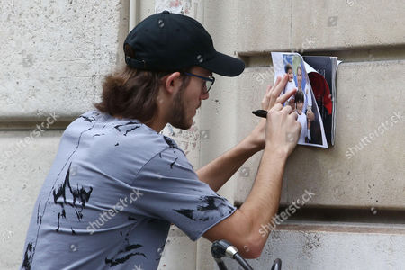 Rene-Charles Angelil signs a photo of himself with his family