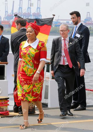 Thobeka Madiba Zuma, wife of South Africa's President Jacob Zuma, left, and Philip May, husband of British Prime Minister Theresa May, leave a ship after a boat tour of the spouses program on the first day of the G-20 summit in Hamburg, northern Germany, . The leaders of the group of 20 meet July 7 and 8