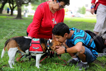 Sammy Garza, right, kisses a therapy dog, Molly, while mother, Del Garza, looks on during a remembrance ceremony in downtown Dallas on . The ceremony outside City Hall paid tribute to five law enforcement officers killed in a sniper attack at a Black Lives Matter demonstration in downtown Dallas on July 7, 2016
