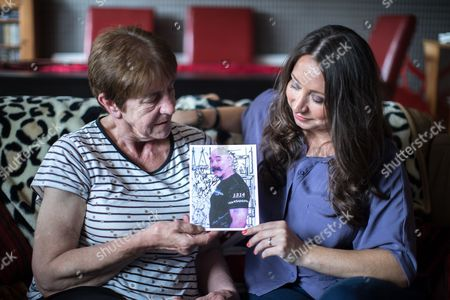 Barbara Dransfield and Paula Williamson pose with a card featuring a photo of Charles Salvador on the front .