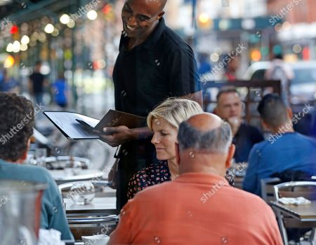 A waiter takes an order for patrons at Lido Harlem on Frederick Douglass Boulevard along Restaurant Row in southern Harlem, in New York. Lido's executive chef is James Beard Award-winning author Serena Bass, caterer to the glitterati. Bass's clients have included Sarah Jessica Parker, Julia Roberts, Keith Richards, Andy Warhol, Andrew M. Cuomo, Marc Jacobs, the New York City Ballet, Estée Lauder, Vanity Fair and Miramax. It's not certain whether Bass's clientele will follow her uptown, where residents are upset about a realtor's name-change from South Harlem to SoHa. Longtime residents say calling Harlem SoHa devalues the neighborhood's rich political and cultural history