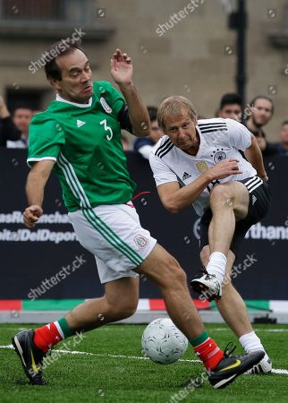"""Jurgen Klinsmann, Fernando Quirarte Germany's Jurgen Klinsmann shoots past Mexico's Fernando Quirarte during a pair of """"revenge"""" matches between former pro players from the Mexican and German national soccer teams in the Zocalo, Mexico City's main square, . The matches pitted against each other former players primarily from the 1986 and 1998 World Cup teams"""